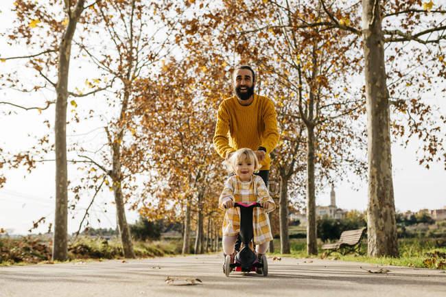 Отец и дочь наслаждаются утренним днем в парке осенью, девушка на скутере — стоковое фото