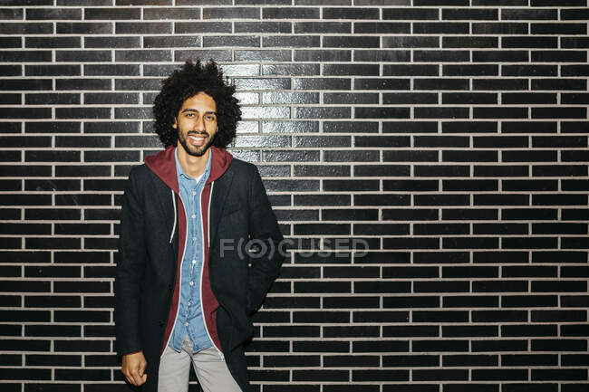 Portrait of a smiling young man standing at a black wall — Stock Photo