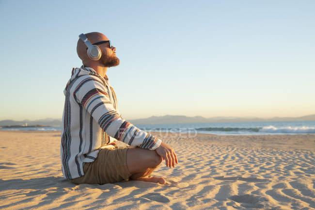 Людина з навушниками сидить на пляжі. — стокове фото
