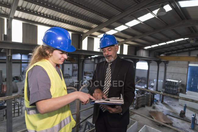 Geschäftsmann mit Ordner im Gespräch mit Arbeiterin in Fabrik — Stockfoto