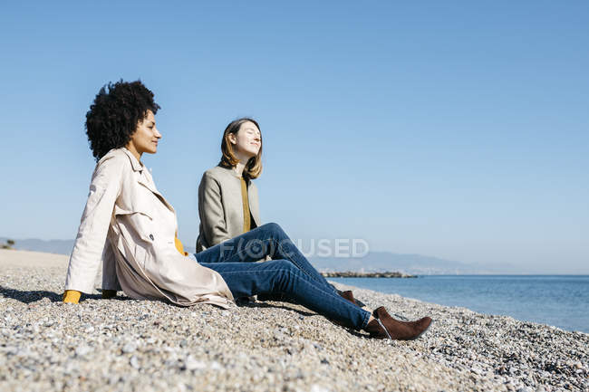 Two friends sitting on the beach enjoying leisure time — стокове фото