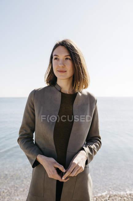 Впевнена жінка стоїть біля моря. — стокове фото