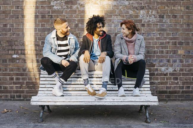 Tres amigos hablando en un banco frente a un muro de ladrillo. - foto de stock
