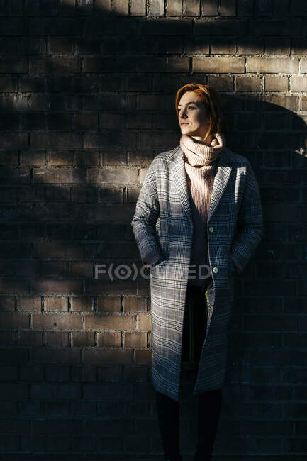 Молода жінка стоїть біля цегляної стіни в тіні і дивиться в сторону. — стокове фото
