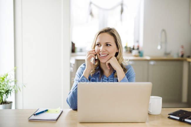 Улыбающаяся женщина с ноутбуком и сотовым телефоном работает дома — стоковое фото
