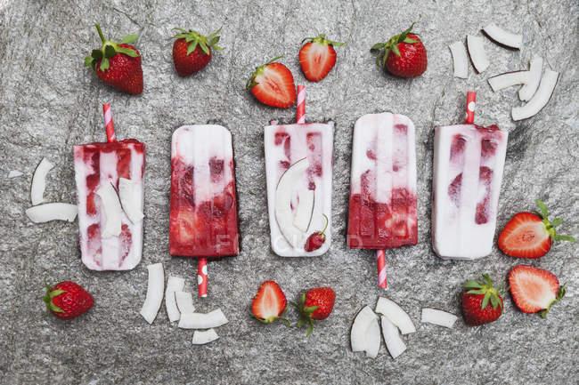 Домашні полуничним кокосовим льодом льодяники зі свіжою полуницею та кокосовими шматочками на граніті — стокове фото