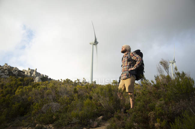 Spain, Andalusia, Tarifa, man on a hiking trip with wind turbine in background — Stock Photo