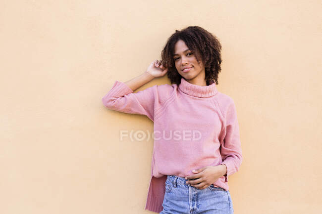 Portrait of smiling young woman wearing pink turtleneck pullover leaning against wall — Stock Photo