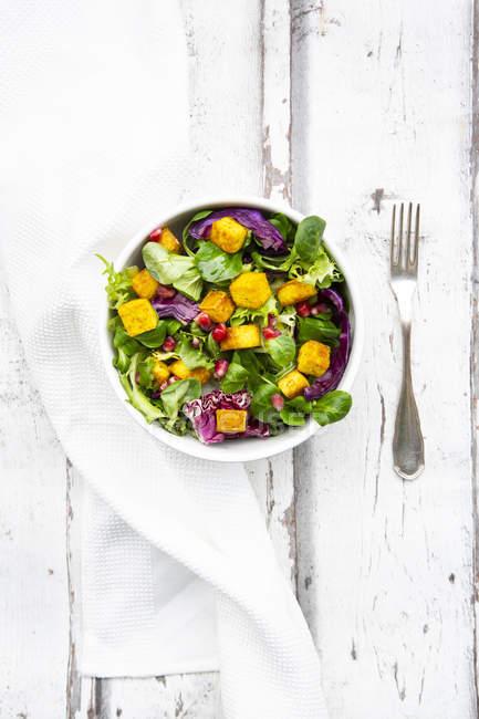 Salade mélangée avec tofu rôti, chou rouge, graines de grenade et curcuma dans un bol sur bois blanc — Photo de stock