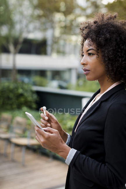 Businesswoman with smartphone and earphones outdoors — Stock Photo
