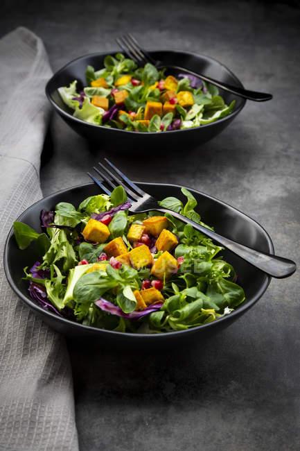 Mixed salad with roasted tofu, red cabbage, pomegranate seeds and curcuma — Stock Photo