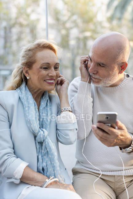 España, Barcelona, feliz pareja de ancianos compartiendo smartphone con auriculares - foto de stock