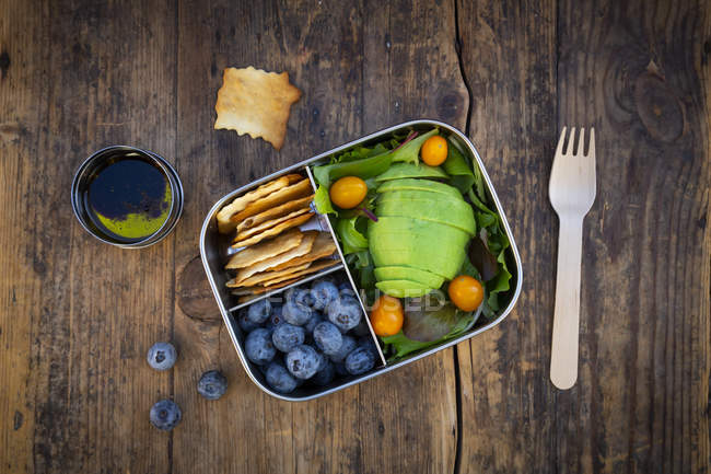Lunch box of leaf salad, avocado, blueberries, tomatoes and crackers — Stock Photo
