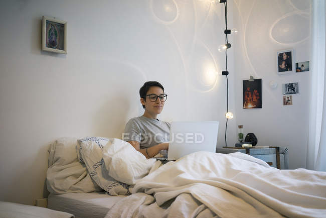 Young woman sitting in bed, using laptop — Stock Photo