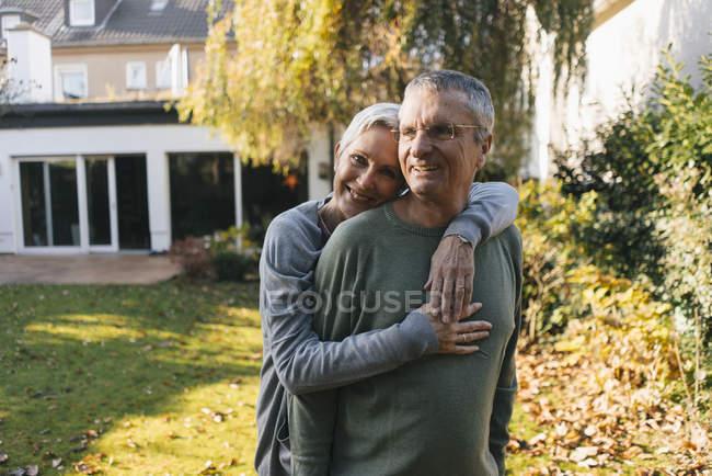 Feliz pareja de ancianos cariñosos abrazando en el jardín - foto de stock