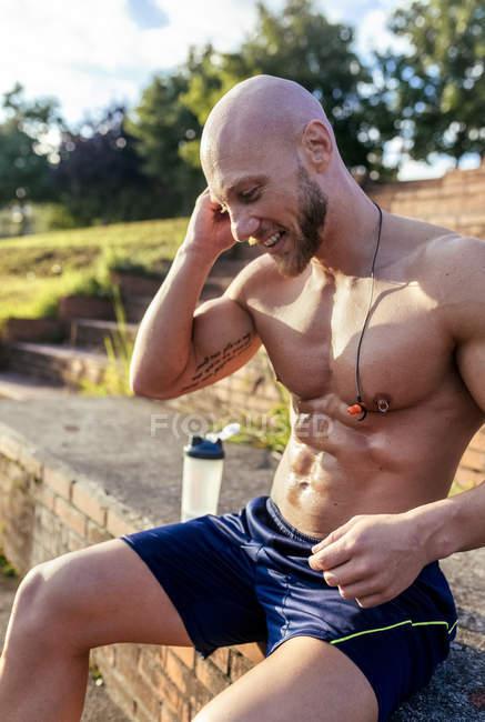 Souriant homme musclé poitrine nue écoutant de la musique après l'entraînement — Photo de stock