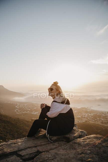 ПАР, Кейптаун, Клоф Нек, усміхнена жінка, що сидить на скелі на заході сонця. — стокове фото