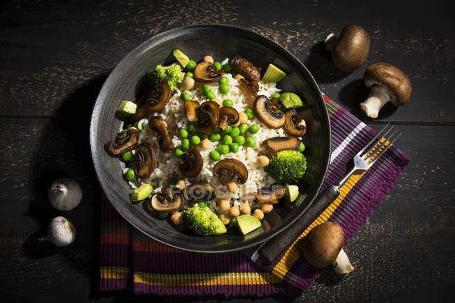 Plat végétalien : riz naturel aux champignons, petits pois, pois chiches, avocat et brocoli — Photo de stock