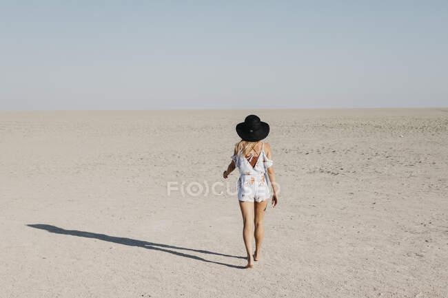 Frau mit schwarzem Hut spaziert in der Wüste — Stockfoto