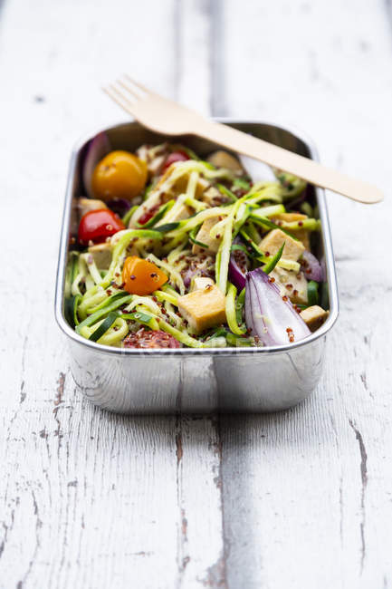 Lunch box of zoodles with fried tofu, red quinoa, red onions and tomatoes — Stock Photo