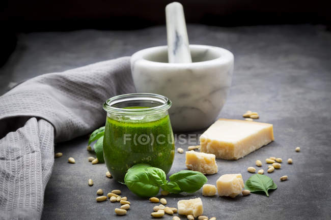 Glass of homemade pesto Genovese, ingredients, mortar and kitchen towel — Stock Photo