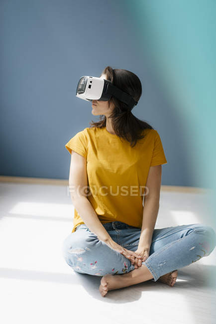Woman sitting cross-legged on floor, wearing VR glasses — Stock Photo