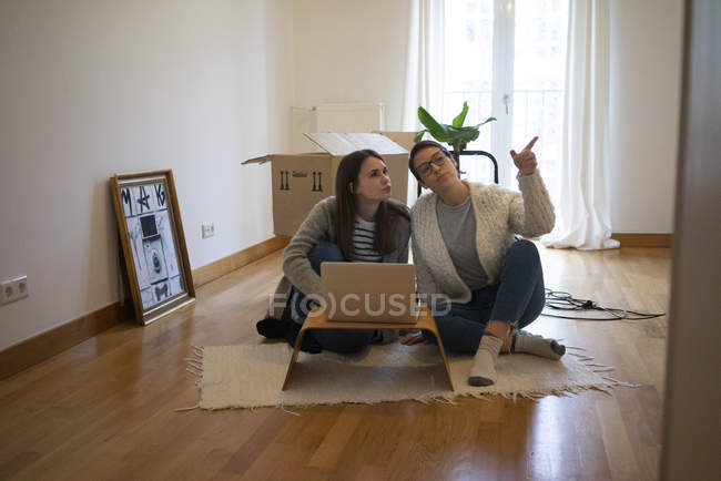 Young women sitting on floor of their new home, using laptop — Stock Photo