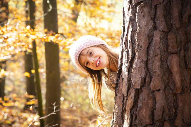 Молодая девушка за деревом осенью — стоковое фото