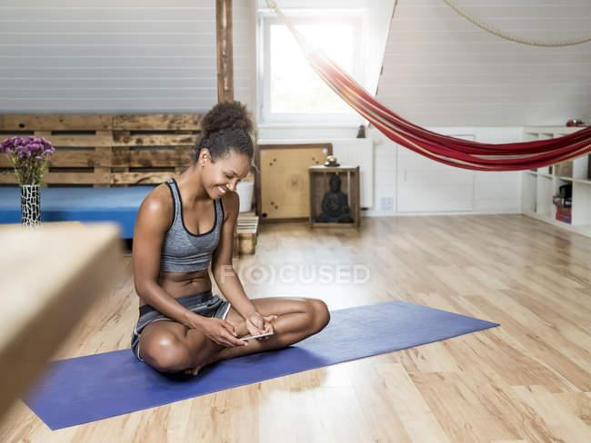 Улыбающаяся молодая женщина сидит на коврике для йоги и смотрит на мобильный телефон — стоковое фото