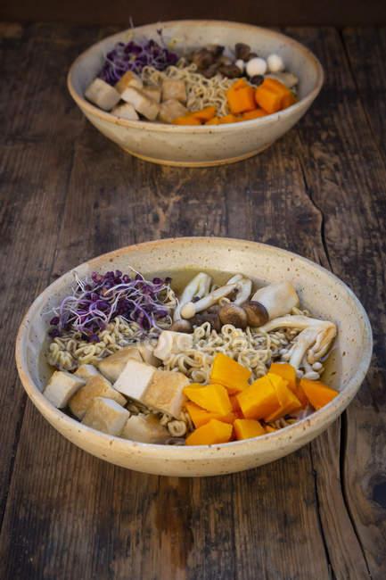Soupe Miso Ramen aux nouilles, pousses de radis rouges, citrouille, tofu frit, shimeji et champignon trompette de roi — Photo de stock