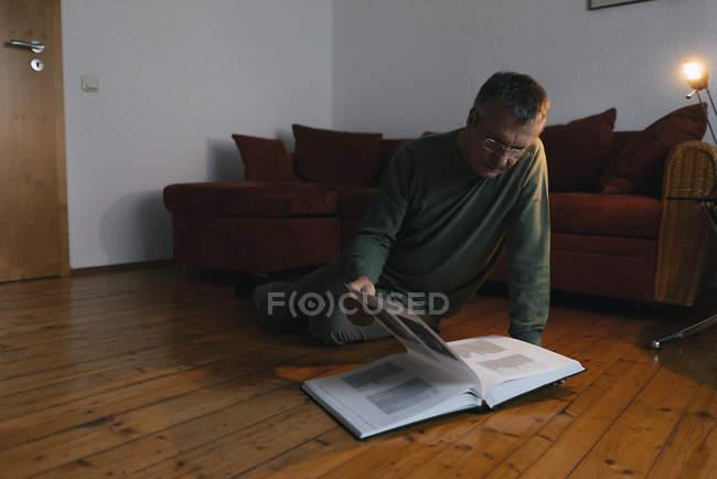 Пенсионер сидит дома на полу и смотрит на фотоальбом — стоковое фото