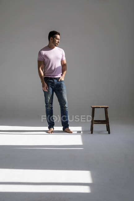 Man standing in a loft in sunshine beside a stool — Stock Photo
