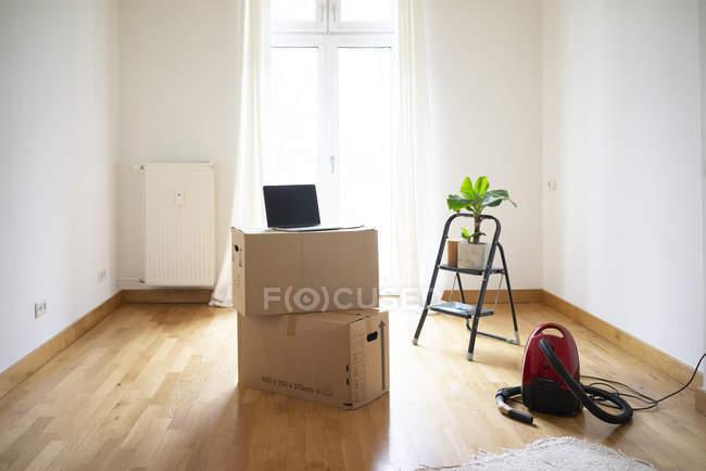 Caixas de papelão empilhadas e laptop em uma sala vazia — Fotografia de Stock