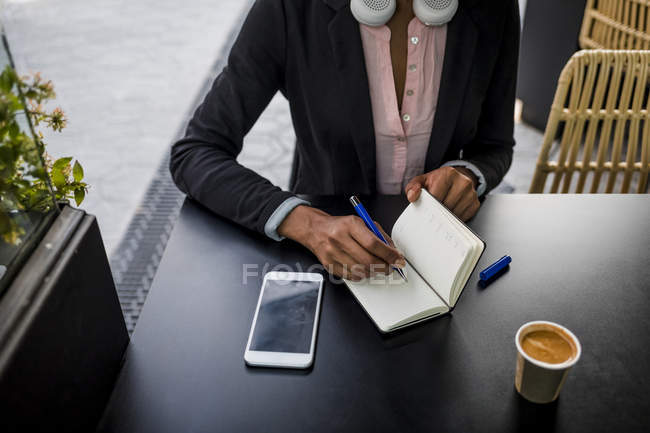 Businesswoman taking notes at pavement cafe, partial view — Stock Photo