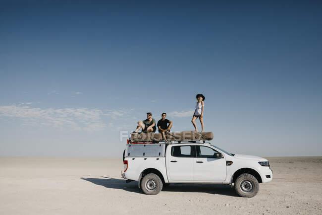 Amici su un safari, in piedi sul loro fuoristrada — Foto stock