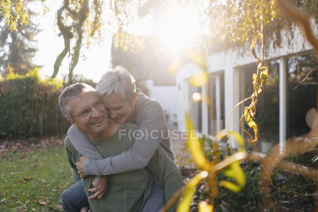 Feliz hombre mayor portador de piggyback esposa en el jardín - foto de stock