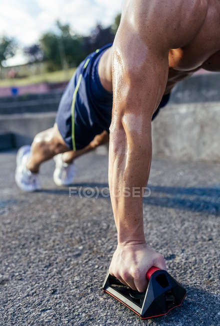 Close-up of barechested muscular man doing push-ups outdoors — Stock Photo
