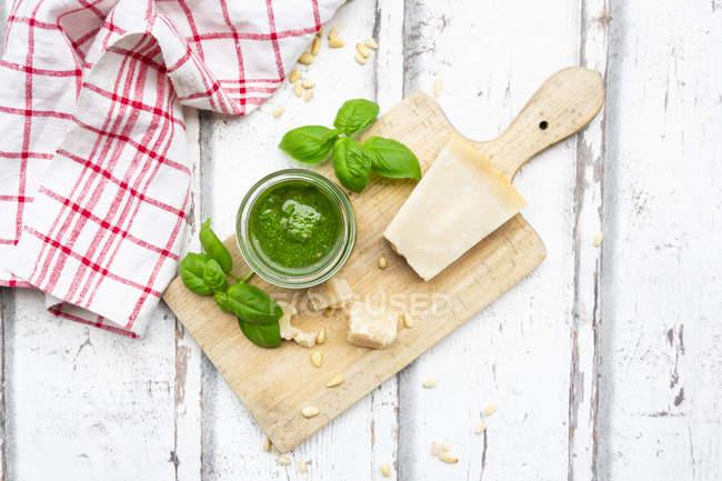 Стакан домашнего песто Дженовезе, ингредиенты и кухонное полотенце — стоковое фото