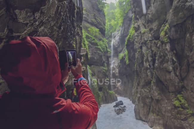 Germania, Baviera, Partnach Gorge vicino a Garmisch-Partenkirchen, uomo con giubbotto antipioggia rosso che scatta una foto con smarthone — Foto stock
