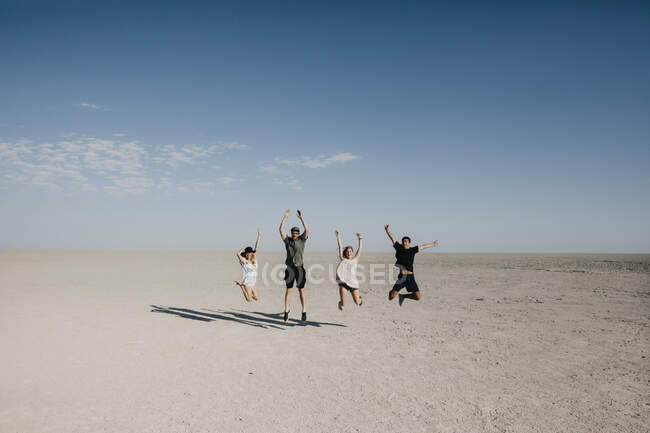 Friends travelling in the desert, jumping for joy — Stock Photo
