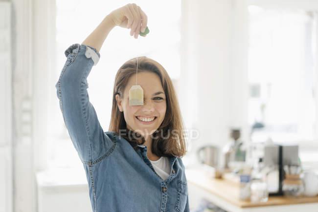 Красивая женщина с чайным пакетиком, улыбающаяся — стоковое фото