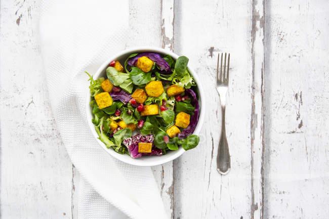 Salada mista com tofu torrado, repolho vermelho, sementes de romã e curcuma em tigela em madeira branca — Fotografia de Stock