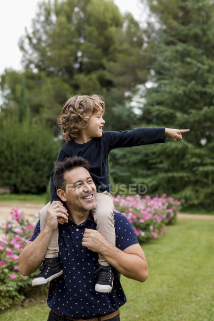Père heureux portant son fils sur les épaules dans le parc — Photo de stock