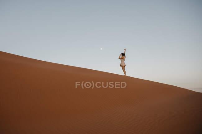Namíbia, deserto de Namib, Parque Nacional Namib-Naukluft, Sossusvlei, mulher em pé na Duna Elim ao pôr do sol — Fotografia de Stock