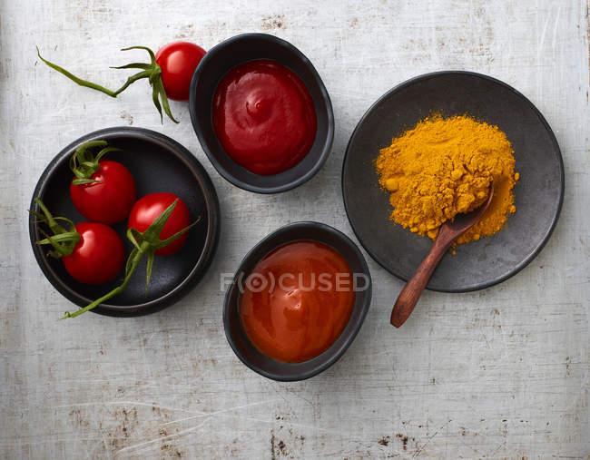 Tomaten, Currypulver, Chili Ketchup und Tomatenketchup in Schüsseln — Stockfoto