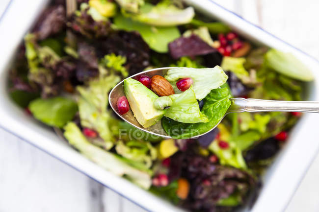 Detox salad bowl with avocado, pomegranate seeds, roasted soybeans, sunflower seeds and nuts, on spoon — Stock Photo