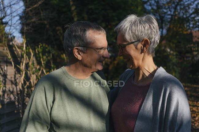 Casal sênior afetuoso de frente para o outro no jardim — Fotografia de Stock
