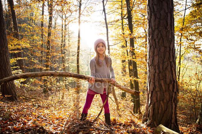 Menina segurando ramo na floresta de outono — Fotografia de Stock