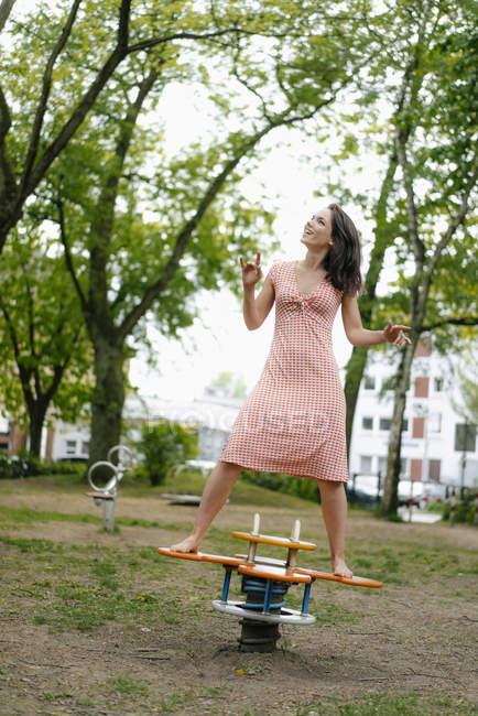 Mulher balanceando em uma mandíbula em um parque infantil — Fotografia de Stock