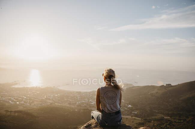 Afrique du Sud, Le Cap, Kloof Nek, femme assise sur le roc au coucher du soleil — Photo de stock